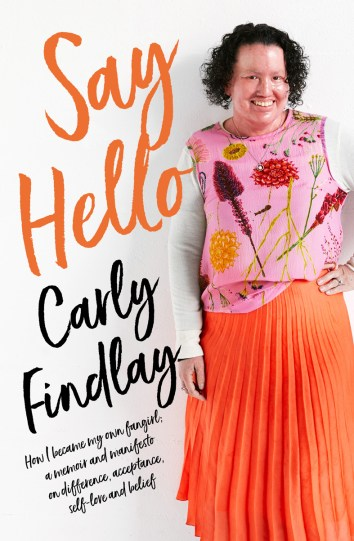 The cover of the book, Say Hello by Carly Findlay. A woman with a red face and short curly hair stands with one hand on her hip. She is wearing an orange skirt and a pink top with flowers on it.