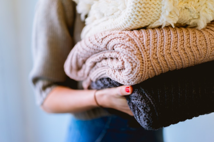 A woman carries a stack of woolen jumpers.