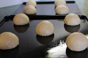 The doughnuts are shaped into balls and left to rise on well oiled baking trays