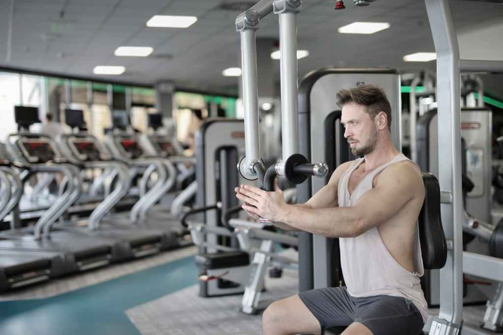 serious sportsman training on exercise machine in modern gym