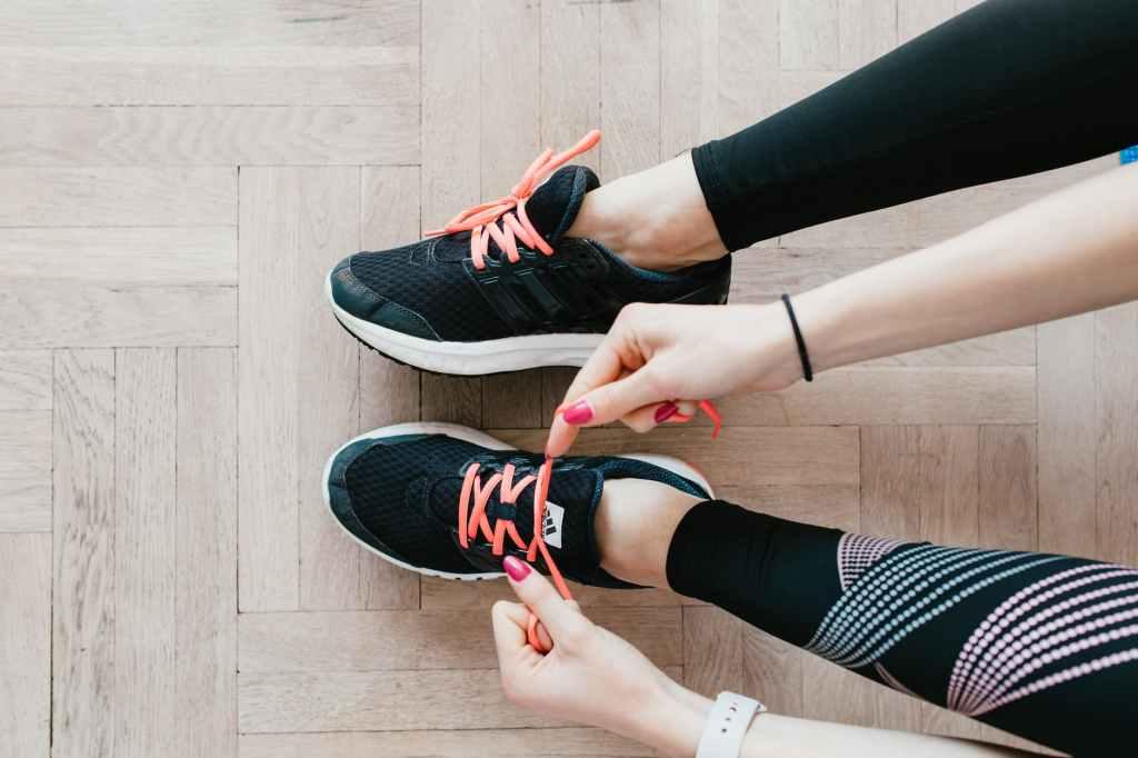 unrecognizable young sportswoman tying sneakers on floor