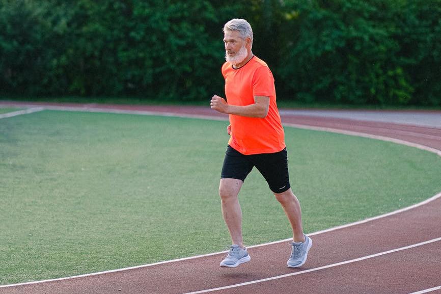 senior man running on racetrack in stadium