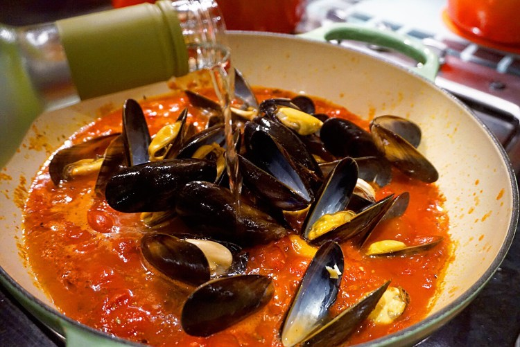 Add the mussels and pour in the white wine. Turn the heat up slightly, cover the pan and cook for 5 minutes.