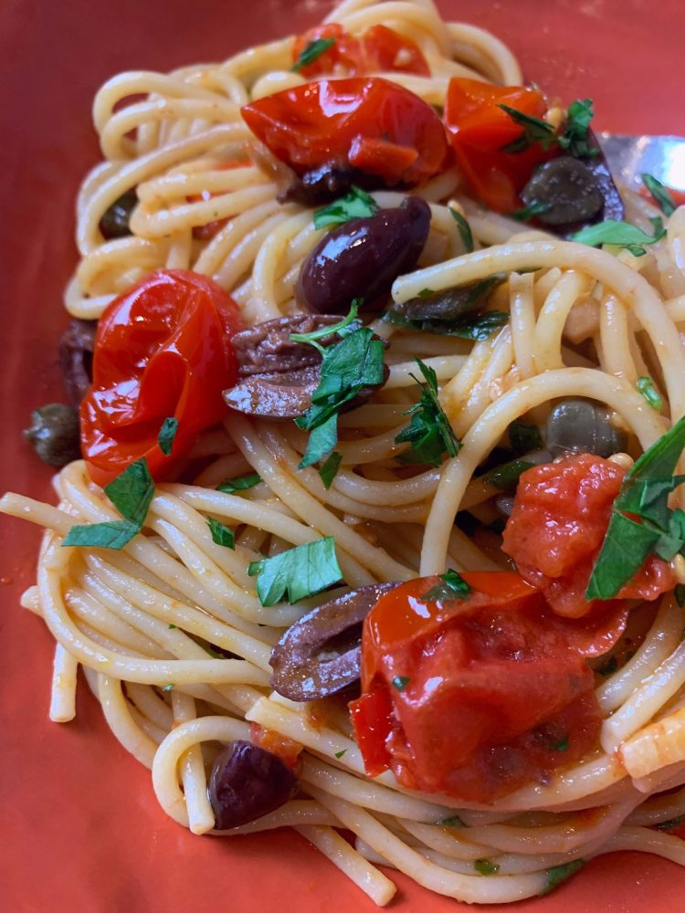 A close up of spaghetti alla puttanesca in a coral cermaic bowl with fresh cherry tomatoes, black olives and capers.