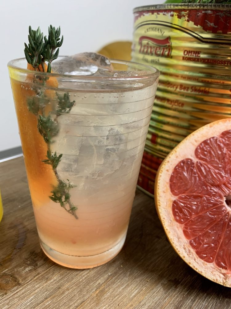 A limoncello and prosecco cocktail with grapefruit juice with a thyme garnish