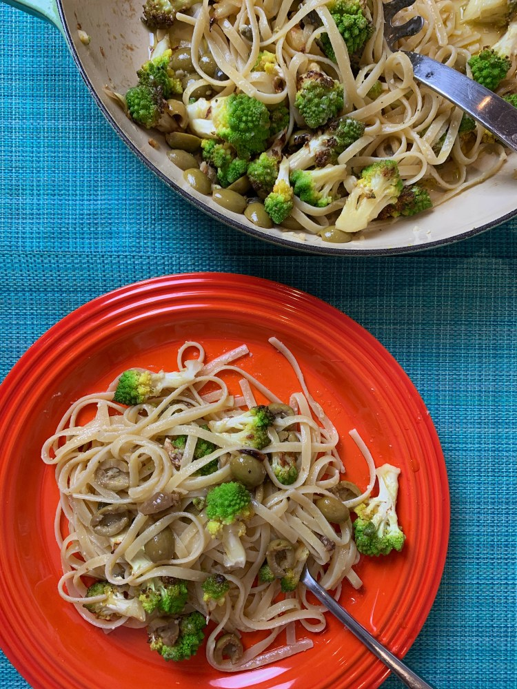 Birds eye view of linguine tossed with broccoli, olives, capers and lemon on a bright orange dinner plate. The remaining in a large pan with spaghetti spoon.