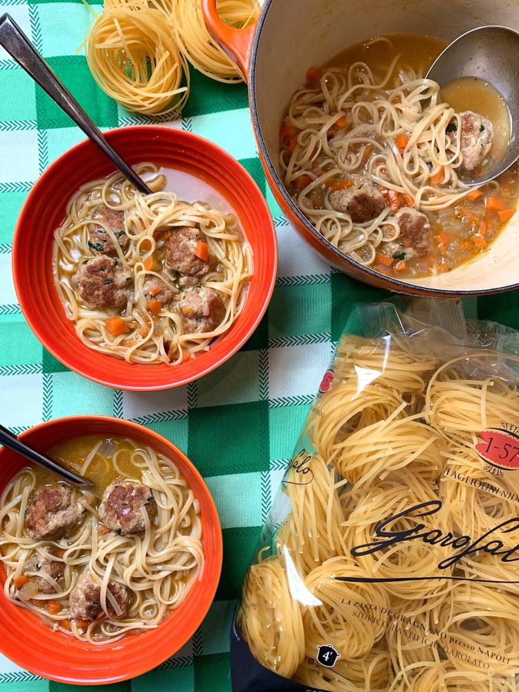 A table set with orange le creuset bowls served with long thin tagliolini pasta and dumplings. There is also a packet of tagliolini nido by Garofalo pasta placed next to them