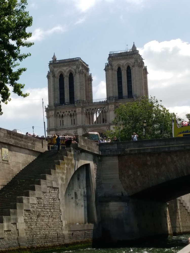 Notre Dame from below with clouds in a light blue sky in the background. Stone stairs lead up from the Seine and the boat is about to go under a low stone bridge.