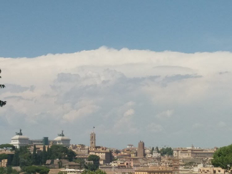 A large cloud bank behind famous buildings in Rome, Italy