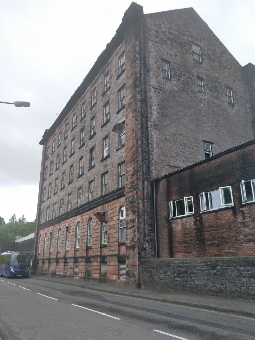 Whisky distillery exterior, brown brick facade, square five story building. There is a road passing in front and there are many windows on each floor.
