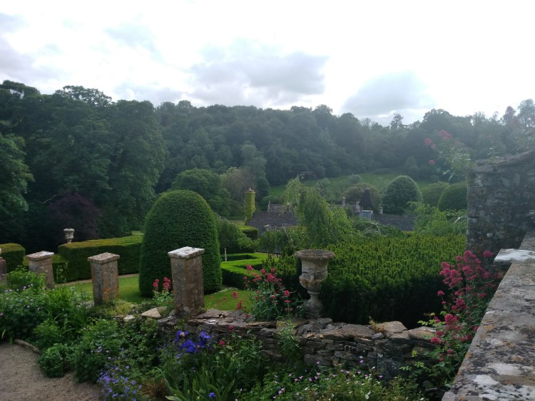 Castle Combe gardens, with many trimmed and orderly bushes. Pockets of blue and pink flowers sprout along the pathway. The sky is cloudy, but bright