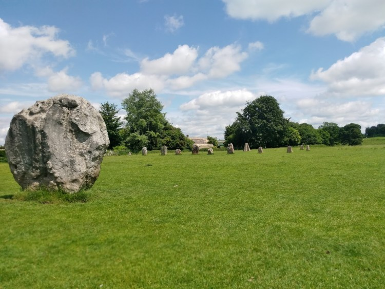 Avebury during the day, one large stone with many smaller ones in a line