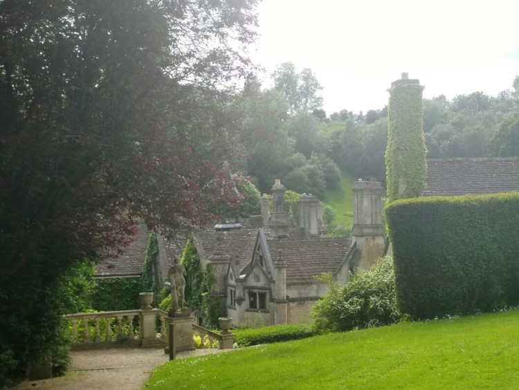 Beautiful topiary and trees with a traditional cotswolds stone house in the distance