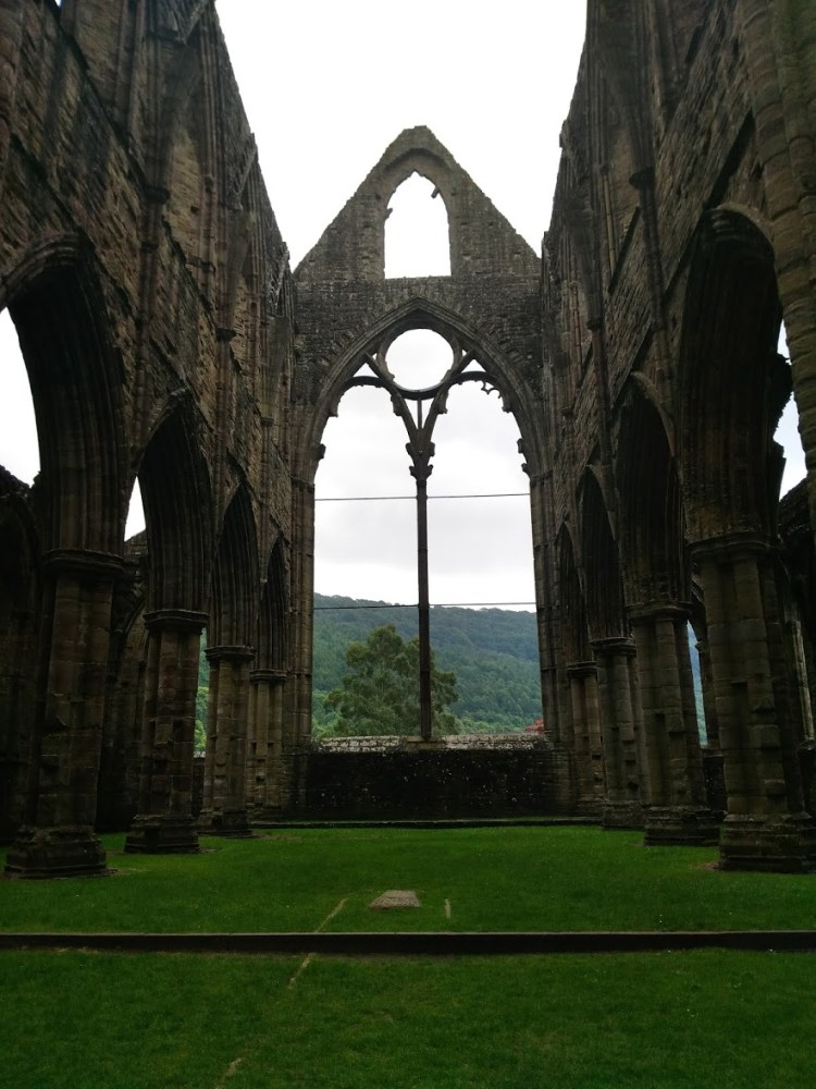 The inside of Tintern Abbey, with huge windows without their stained glass