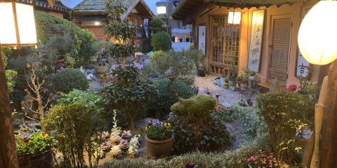 Garden scene in the evening. Two lanterns on either side of the porch. Bushes and a small pond.