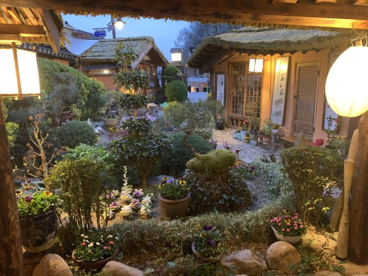 Go in korea Garden scene in the evening. Two lanterns on either side of the porch. Bushes and a small pond.