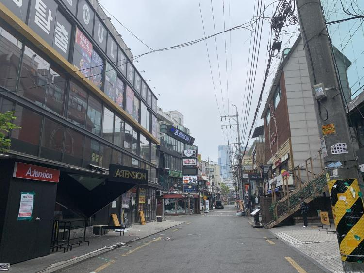 hongdae in the early morning, taken down a street with buildings on either side. Grimy, telephone wires crisscross overhead