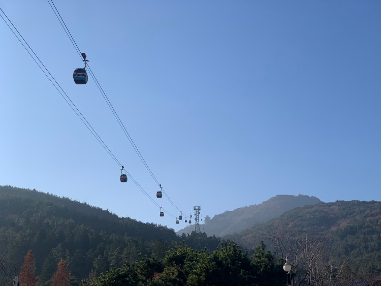 Cable cars going above shorter tree-covered mountains, backdropped against a blue sky. Tongyeong travel guide