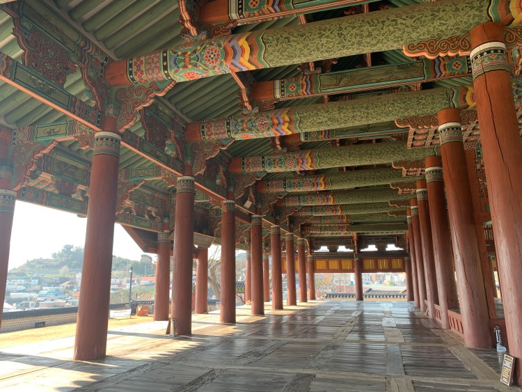 A large traditional Joseon-era hall in green and brown. Many wide pillars and heavily decorated beams Tongyeong travel guide,