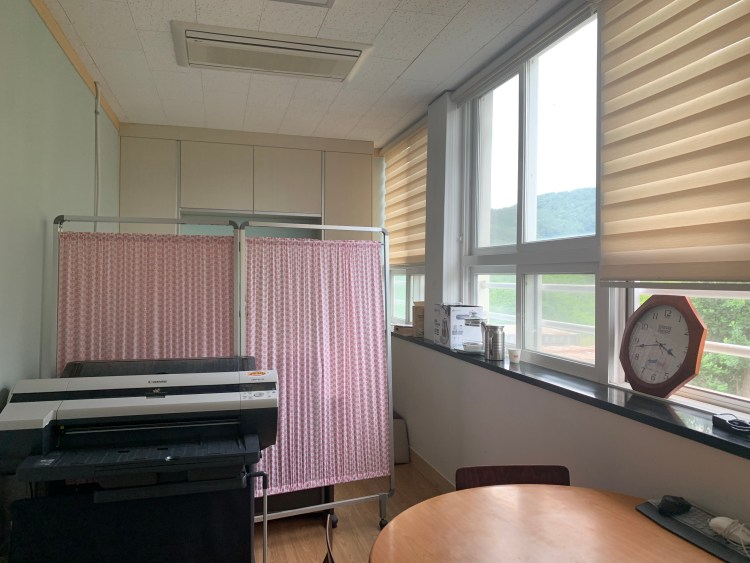 A small single person office with a wall of windows on the right side. There is a pink divider through the middle of the room, a large poster printer, and a small round table with a few chairs. Just a day teaching in Korea!