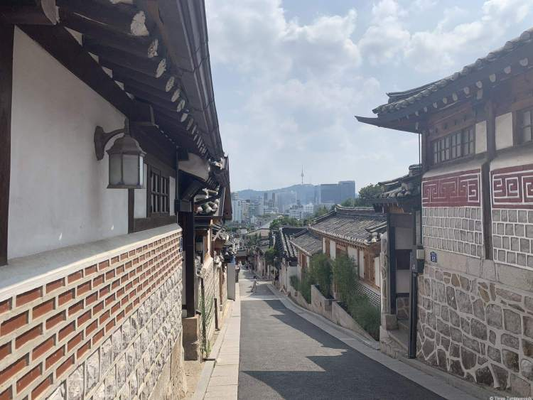 hanok village street with traditional houses seoul travel gudie. The base of the building is in stone with brick runners. The sky is filled with white clouds.