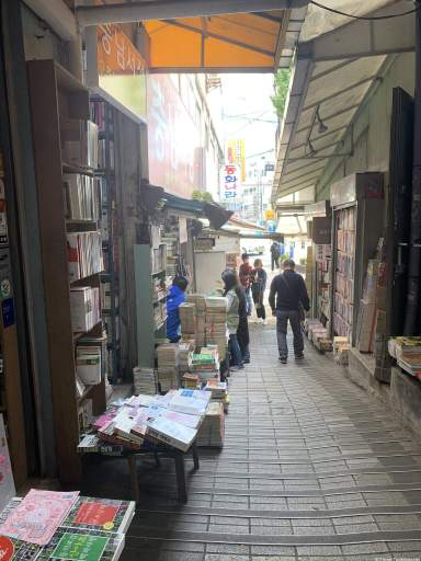 an alley lined with bookshelves. Many books are on benches to display their covers Busan travel guide. The alley is paved with grey blocks and is covered with tarps.