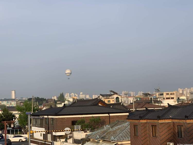 A view of the city within the walls of Suwon travel guide. A hot air balloon floats over the buildings.