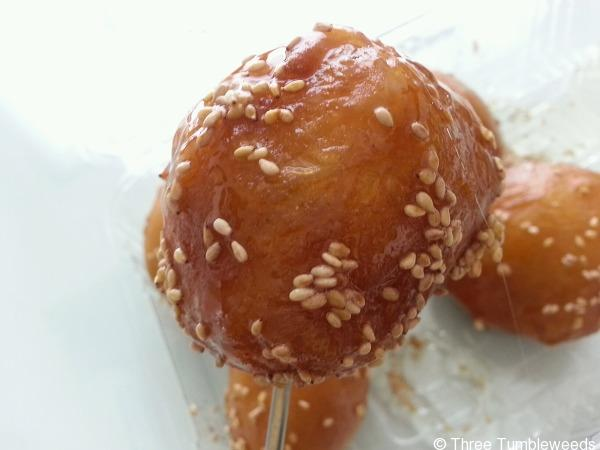 A piece of sticky brown bread shaped into a ball. It is dotted with sesame seeds against a white background.
