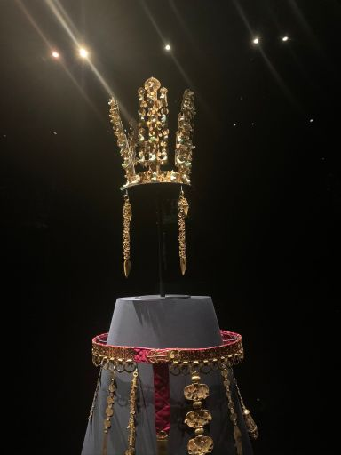 a large gold crown and gold belt suspended in front of a black backdrop. The crown has three main stems with flower-petal-like designs in gold. The belt is a red velvet base with a main center dangling piece of diamond gold plates, with dangling chains around the whole thing.