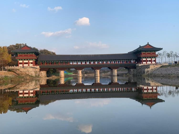 a slightly off kilter image of a Korean bridge reflecting into the river water below. It's a covered bridge with two large two story pavilions on either side as entrances.