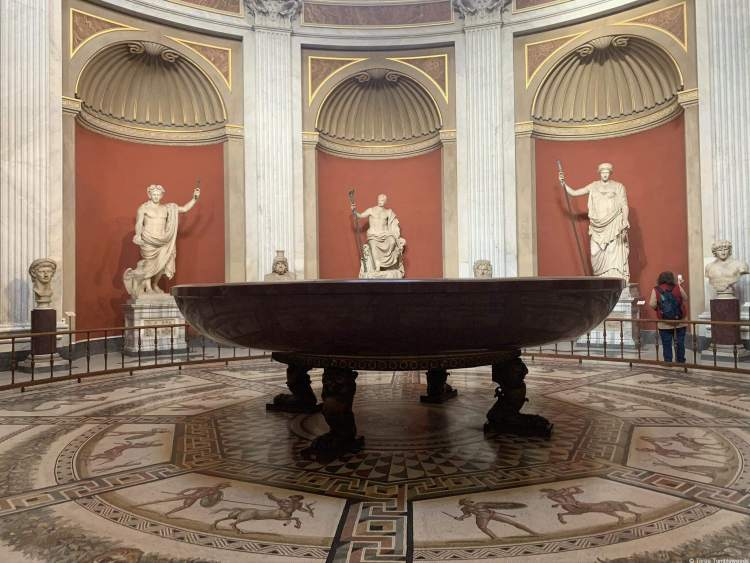 a giant dark red bowl supported by four feet. Three alcoves with statues are in the back of the circular room vatican travel guide