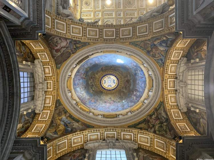 A lavishly decorated cupola with four arched windows with golden aches. The inside of the dome is a biblical scene in shades of blue vatican travel guide.