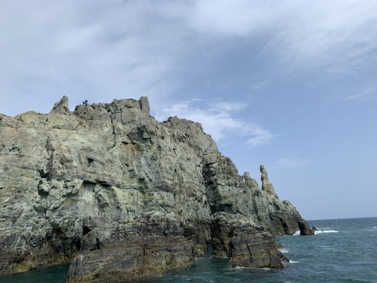 Geoje island rocky island cliff formations. Dark blue water and a light blue sky with some thin clouds frame tall rock formations with large pointy spires sticking up as natural rock formations.