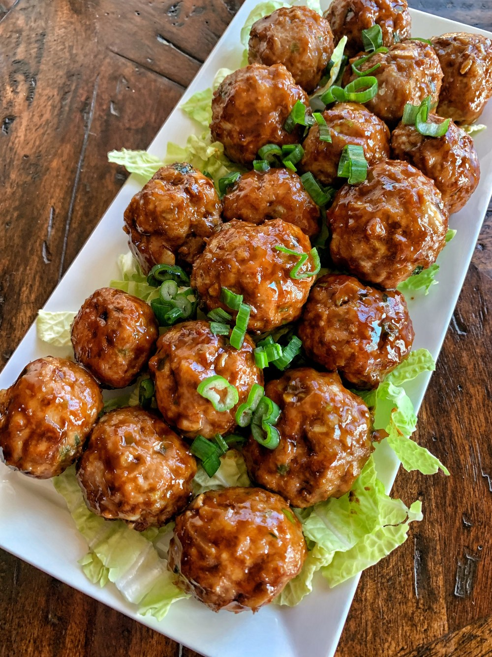 Overhead shot of meatballs made with pork and peanuts on a white plate with green onions and a glaze.