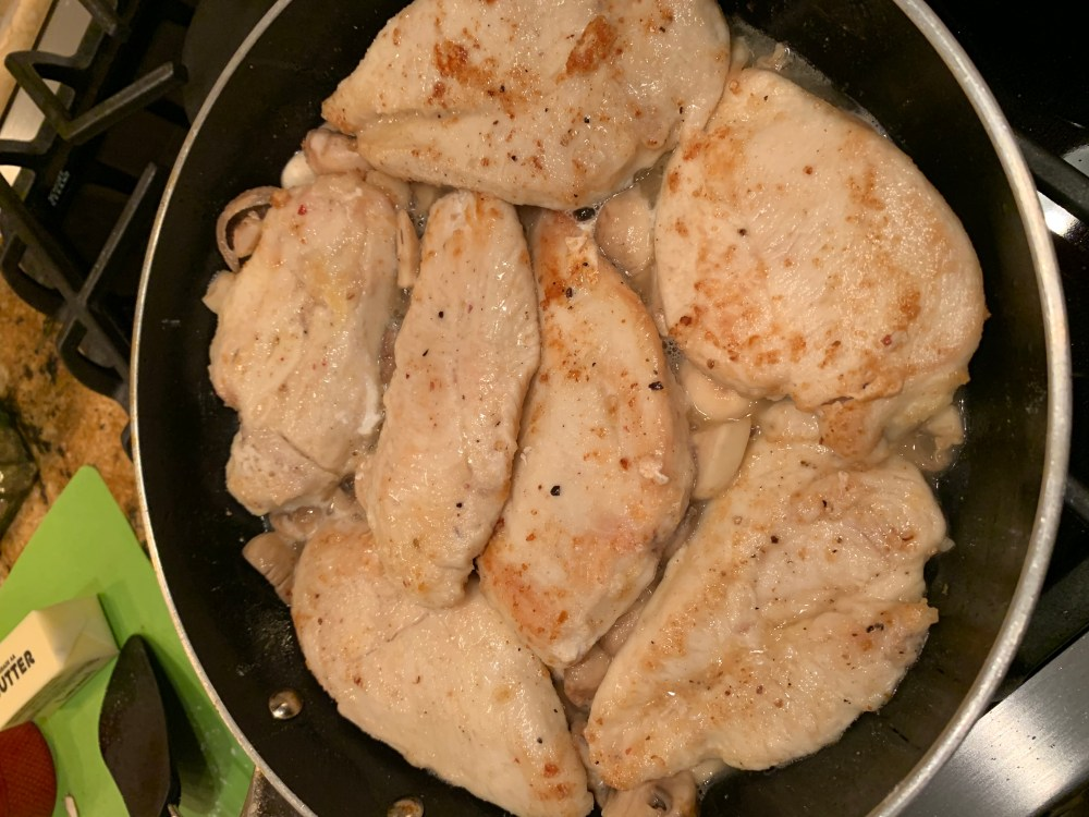 skillet with chicken breasts and mushrooms and white wne sauce cooking on the stove