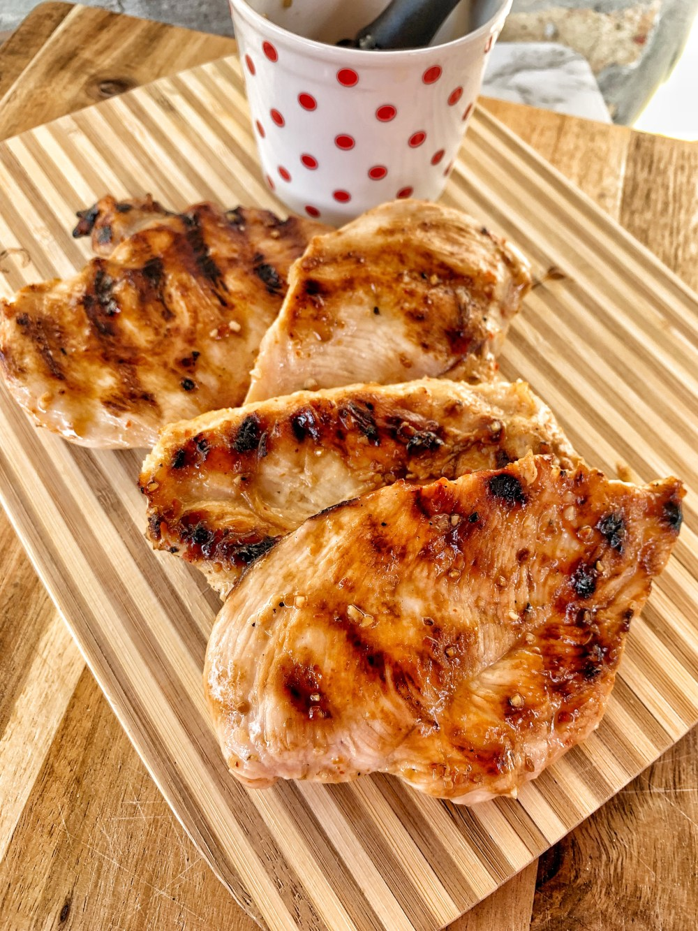 3 cooked chicken breasts with grill marks and a white cup with red polak dots that has italian dressing in it.