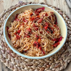 A bowl of pasta with tomatoes and olive oil.
