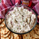 Bowl of party dip surrounded by crackers and the jar of hormel dried beef. Pictured is also a pink dish towel.