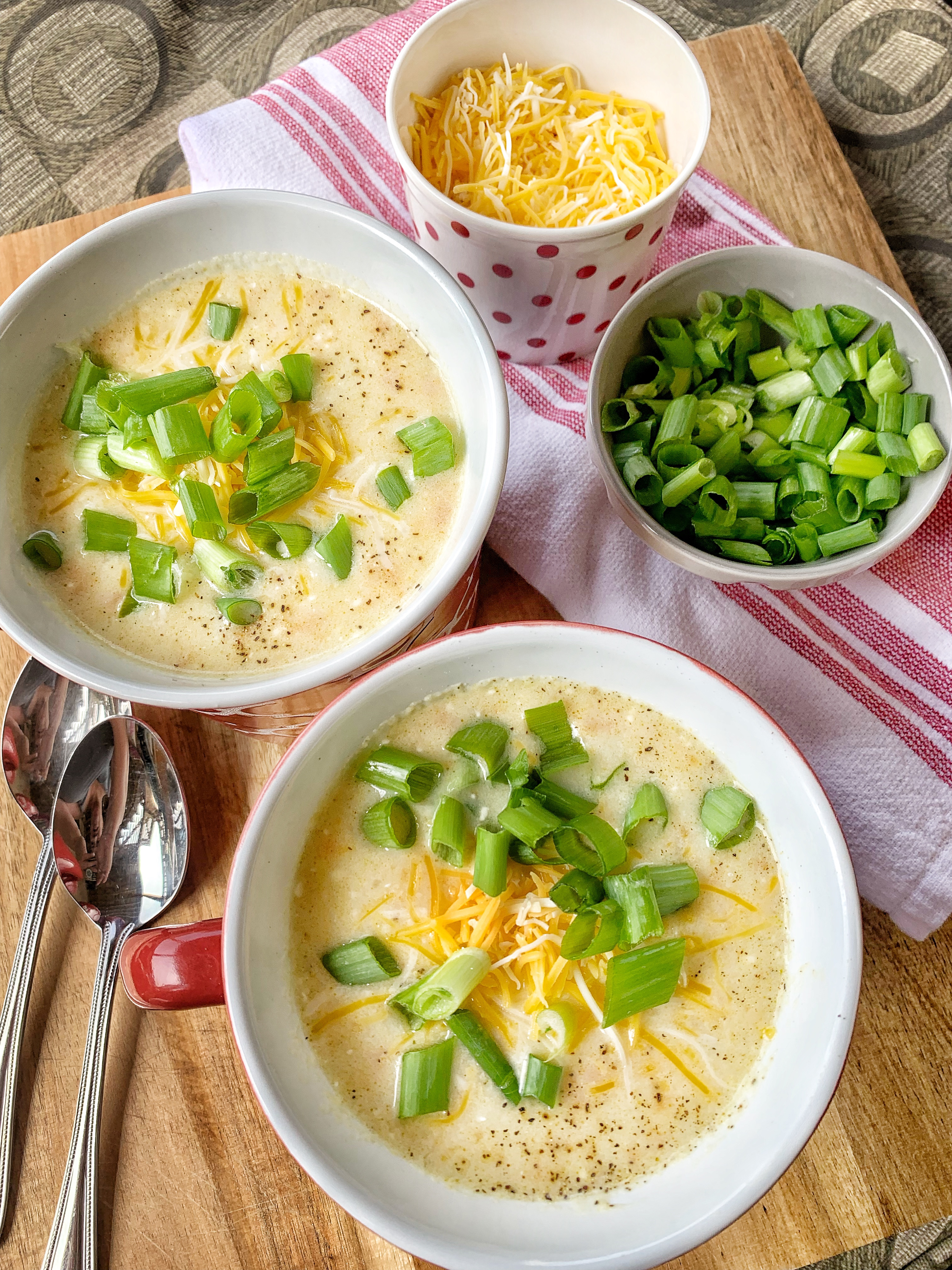 two mugs of potato soup with green onions and cheese.