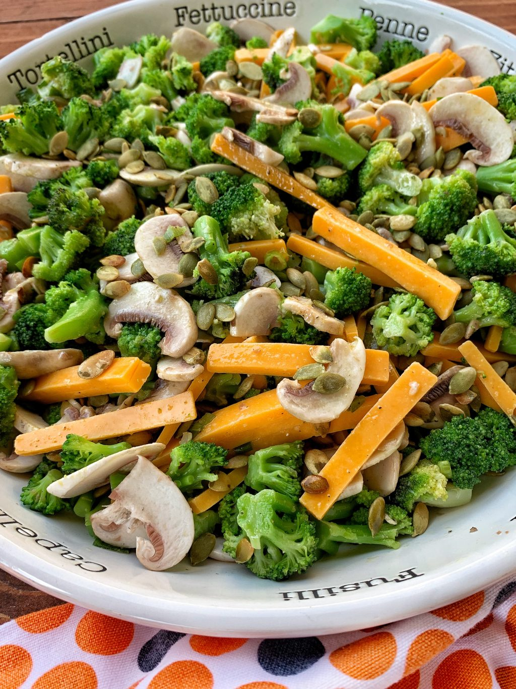 white bowl with bright green broccoli, cheddar cheese slices and mushrooms