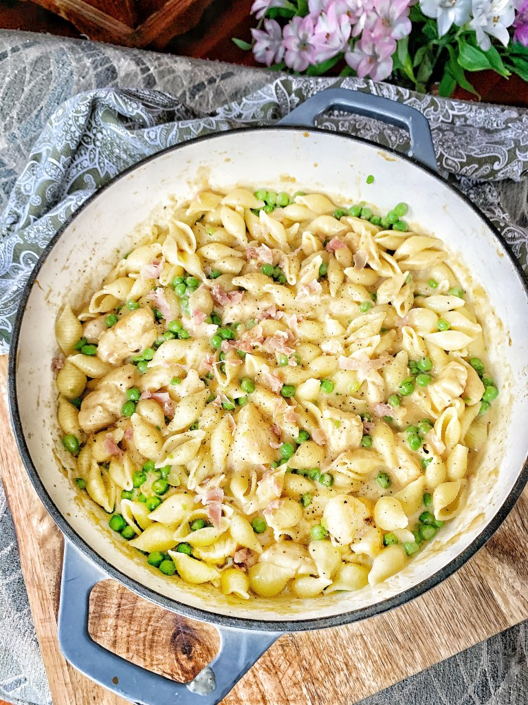 Skillet with pasta shells, chicken, peas, prosciutto and cheese sauce
