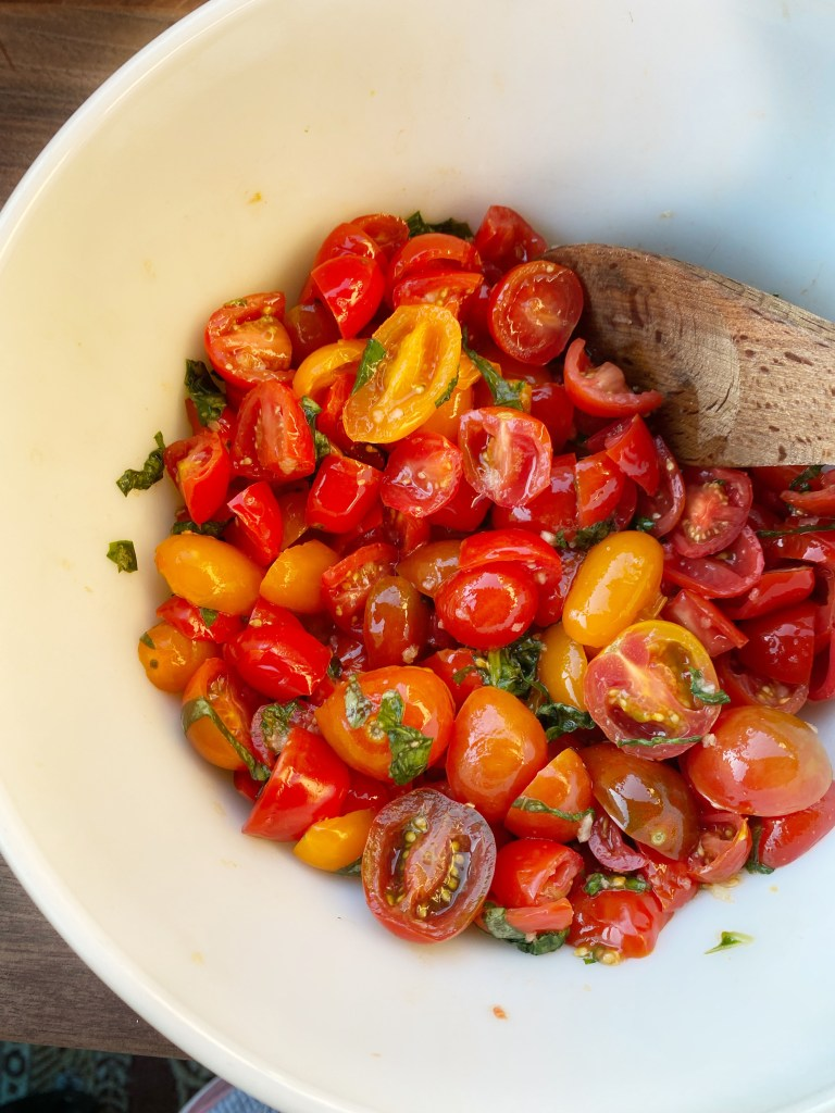 Diced tomatoes with kosher salt and garlic in a bowl.