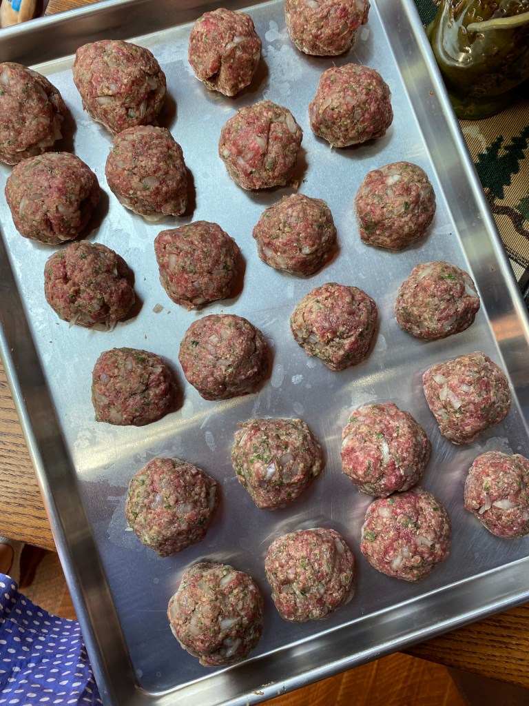 A sheet pan full of beef meatballs waiting to be cooked.