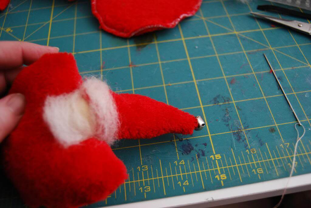 Sew a tiny jingle bell to the very tip of the hat. (or hot glue)