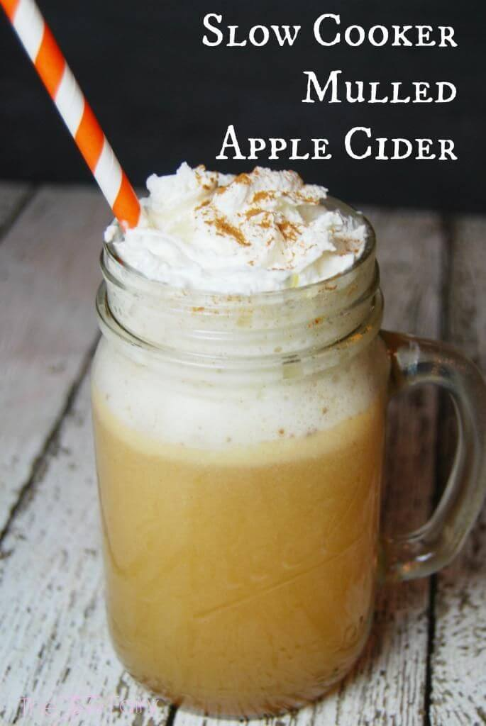 A mason jar mug full of mulled apple cider topped with whipped cream, cinnamon, and a straw.