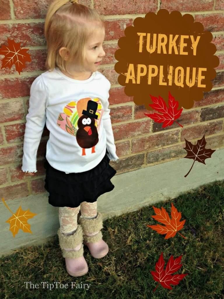 A little girl wearing a turkey shirt.