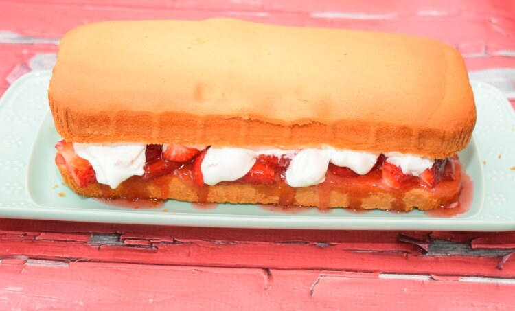 The pound cake sandwich layers with layers of strawberries and whipped cream between them.