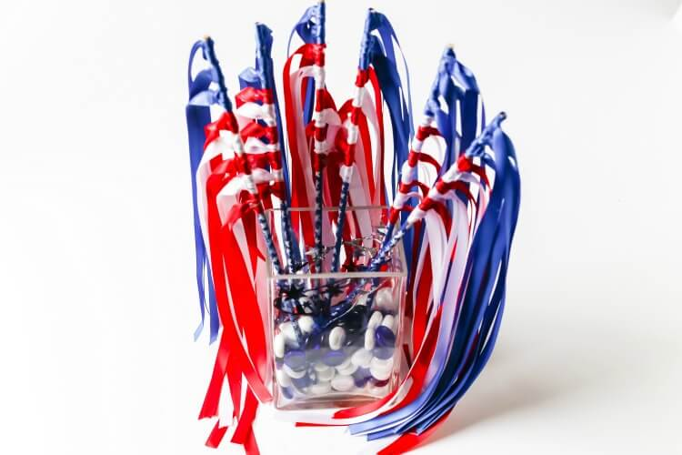 A vase full of DIY Patriotic Flag Waving Wands.