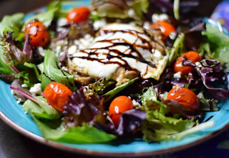 Low Carb Sheet Pan Caprese Chicken Thighs over salad close up