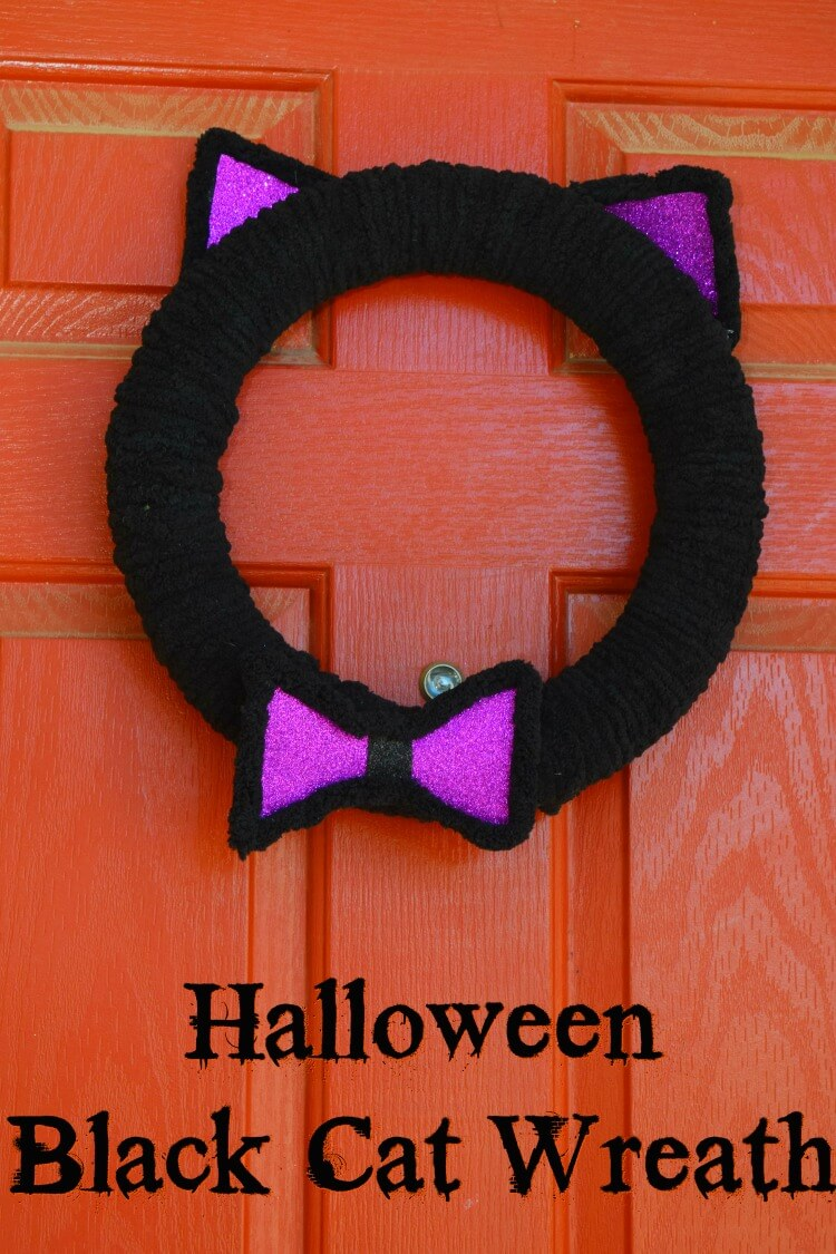 Black Cat Wreath with purple ears and bow tie on the front door.